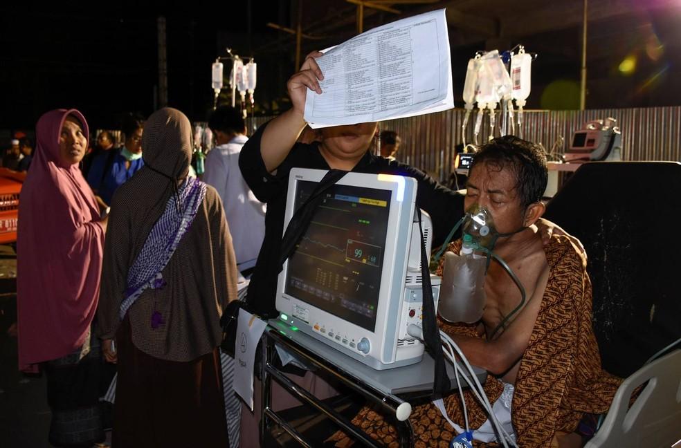 Paciente é levado para fora de prédio de hospital na ilha de Lombok após terremoto que deixou pelo menos 82 mortos neste domingo (Foto: Antara Foto/Ahmad Subaidi via Reuters)