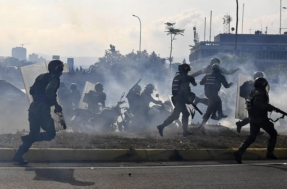 Membros da Guarda Nacional Bolivariana em defesa de Nicolás Maduro correm em meio a gás lacrimogêneo após tiros de rifle disparados por guardas que defendem o oposicionista autodeclarado presidente interino Juan Guaidó em frente à base aérea 'La Carlota', em Caracas — Foto: Yuri Cortez/AFP