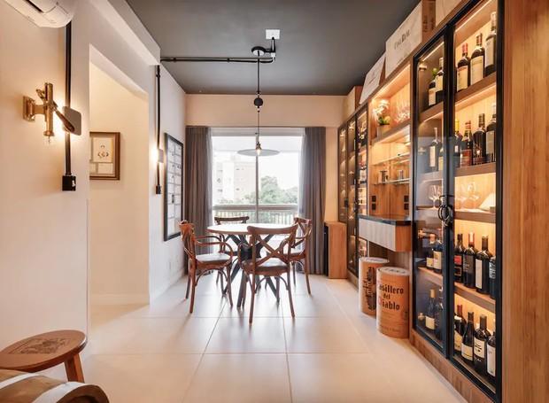 A parede ao lado da porta é coberta por armários que exibem os rótulos lado a lado. Os detalhes na decoração, como os cabos de iluminação expostos dão uma aparência industrial ao apartamento (Foto: Airbnb/ Reprodução)