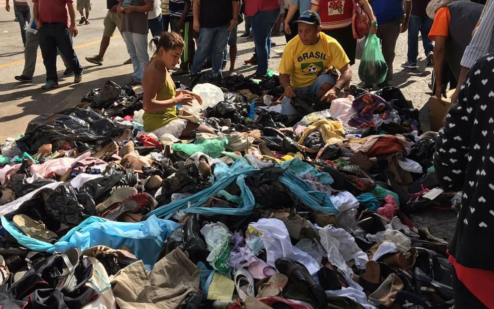 Mulher procura alguma peça de roupa em meio a pilha de doações no Largo do Paissandu (Foto: Glauco Araújo/G1)
