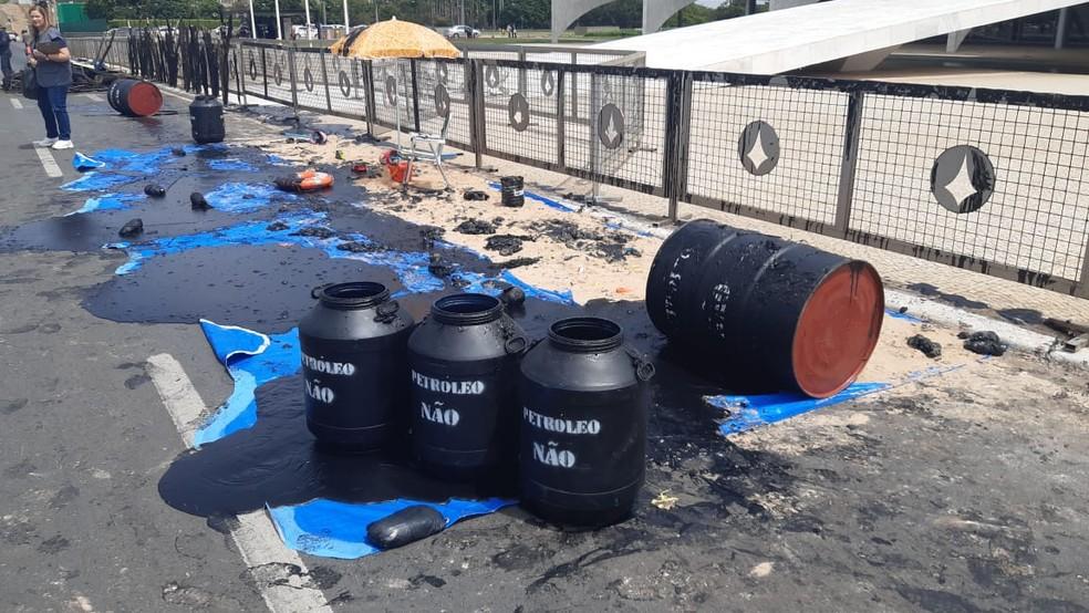 Ambientalistas do Greenpeace derramaram tinta preta em frente ao Palácio do Planalto, em Brasília, para chamar a atenção sobre o óleo que chega às praias do Brasil — Foto: Carolina Cruz/G1