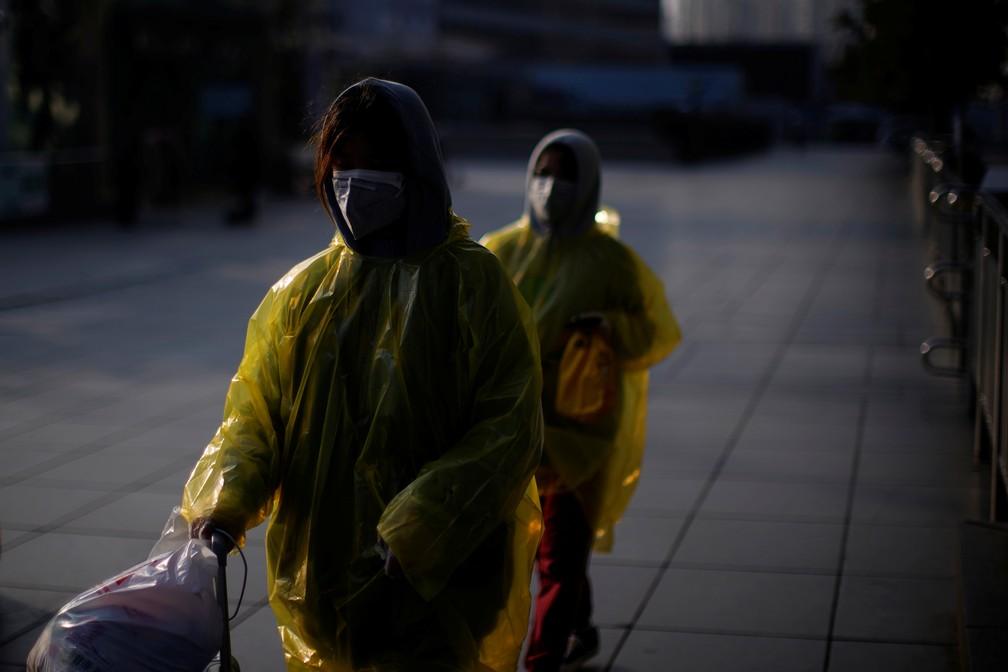 Mulheres vestindo máscaras e capa de chuva como proteção contra o coronavírus em Xangai, China — Foto: Aly Song/Reuters