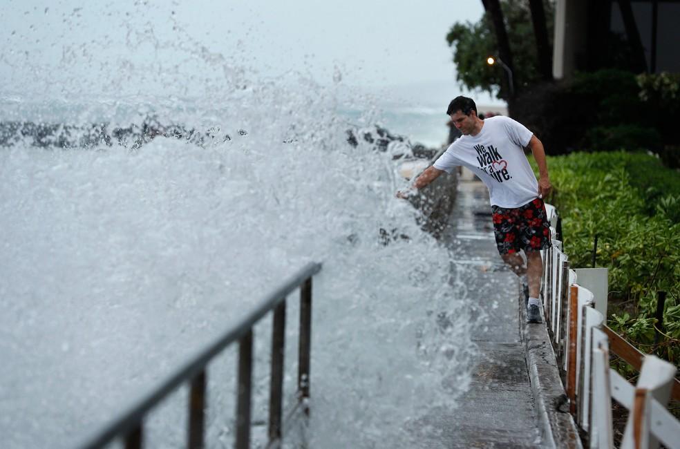 Homem evita ser atingido por uma onda em uma passarela na quinta-feira (23), em Honolulu, no Havaí  (Foto: John Locher/AP)