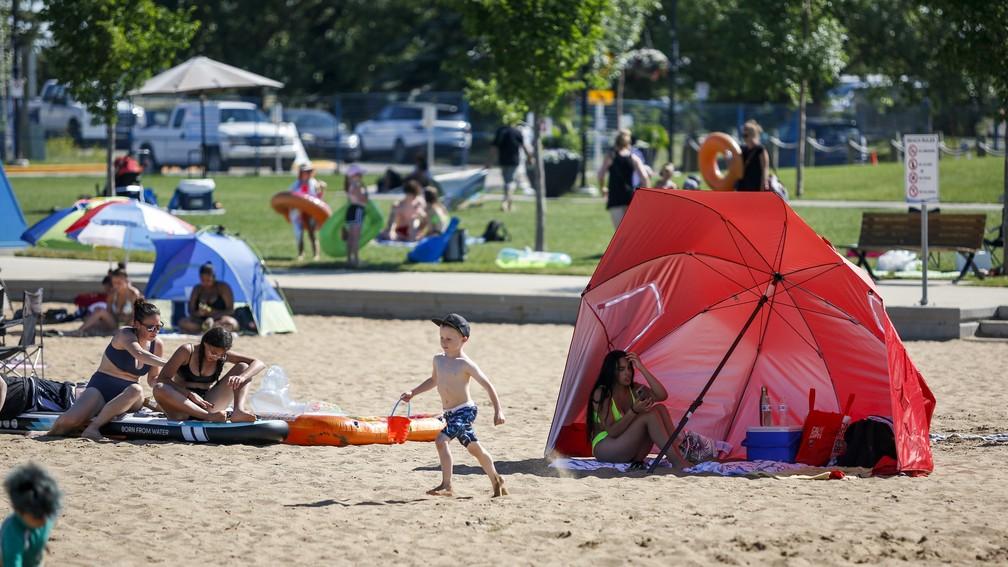 Pessoas tentam se refrescar do calor em Chestermere, na província de Alberta, na terça-feira (29), no Canadá — Foto: Jeff McIntosh/The Canadian Press via AP