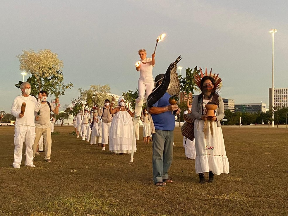 """Sobre pernas de pau e carregando uma tocha, artista se destaca durante performance """"Quem partiu é o amor de alguém"""", em Brasília — Foto: Larissa Passos/ G1"""