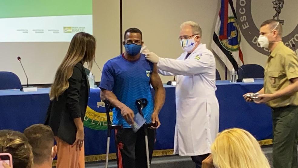 O remador paralímpico Michel Pessanha é vacinado pelo ministro da Saúde, Marcelo Queiroga — Foto: João Gabriel Rodrigues