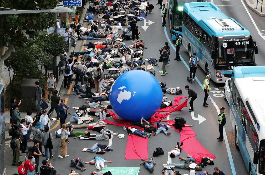 Manifestante simulam morte para alertar sobre o aquecimento global — Foto: Yonhap via Reuters