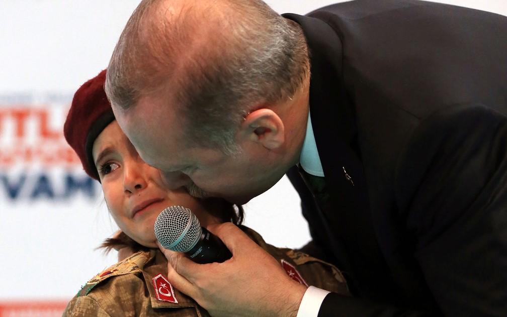 O presidente da Turquia, Recep Tayyip Erdogan, beija a menina Amine Tiras, de 6 anos, durante congresso de seu partido na cidade de Kahramanmaras, no sábado (24) (Foto: Murat Cetinmuhurdar/Pool Photo via AP)
