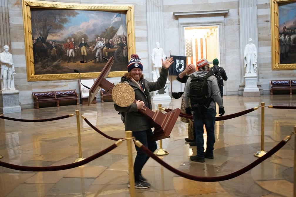 Invasor carrega púlpito da presidente da Câmara dos EUA durante ato no Capitólio. O homem foi preso, informou a imprensa americana neste sábado (9) — Foto: Win McNamee / GETTY IMAGES NORTH AMERICA / Getty Images via AFP