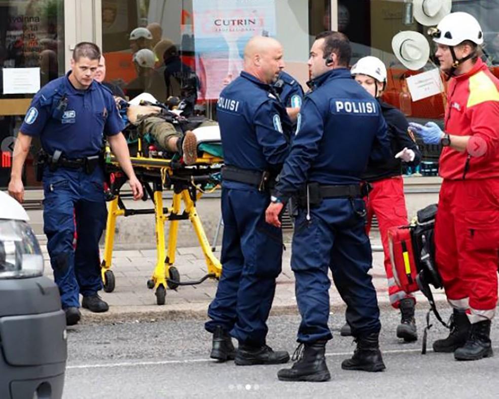 Policiais em torno de uma pessoa ferida na maca (Foto: Jennifer KATSAMANTOU / AFP)