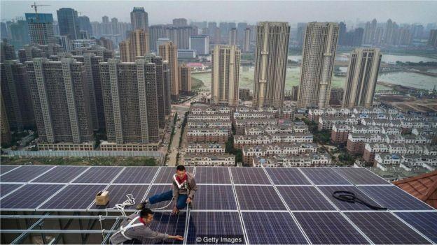 Devido à ineficiência de transmissão de eletricidade por longas distâncias, os painéis solares de terraços tendem a ser mais eficientes do que as remotas fazendas solares (Foto: KEVIN FRAYER/BBC)