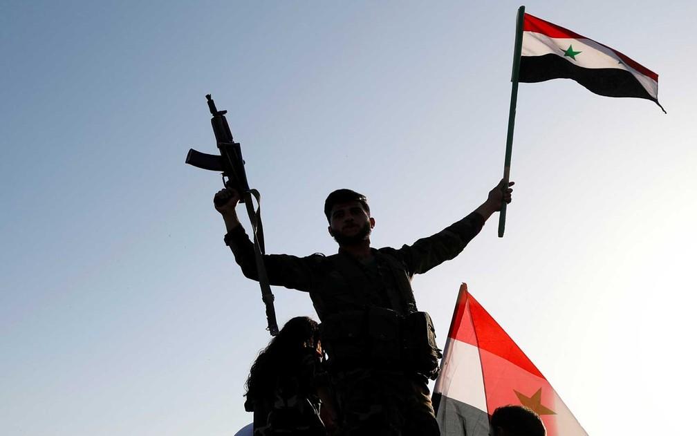 Soldado sírio armado agita bandeira contra ataques aéreos (Foto: Omar Sanadiki / Reuters)