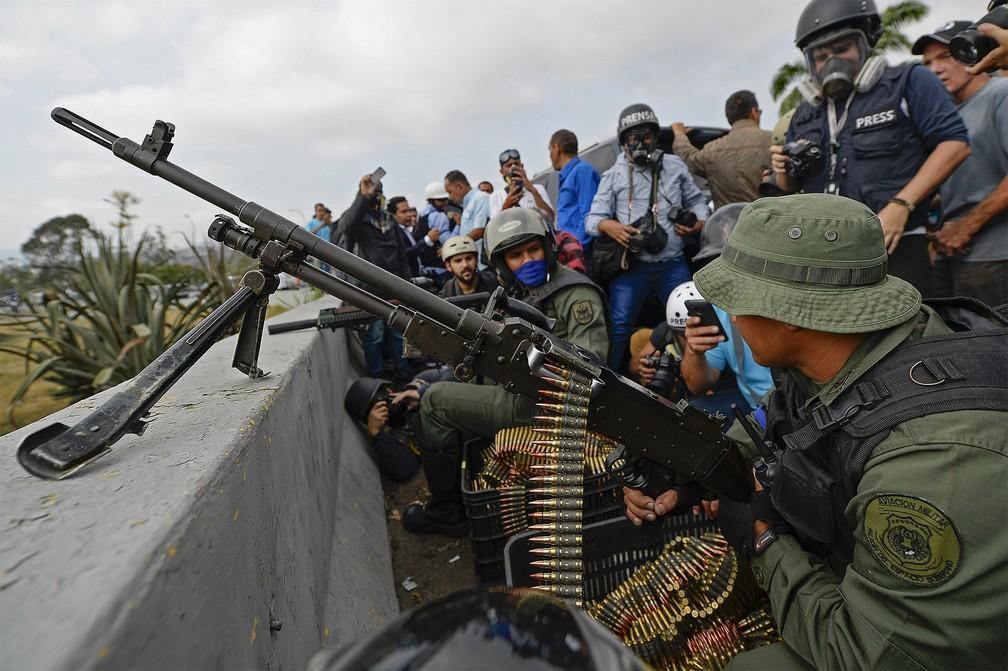 Militares apoiadores de Guaidó se posicionam com fuzis duante da base aérea 'La Carlota', em Caracas — Foto: Matias Delacroix/AFP