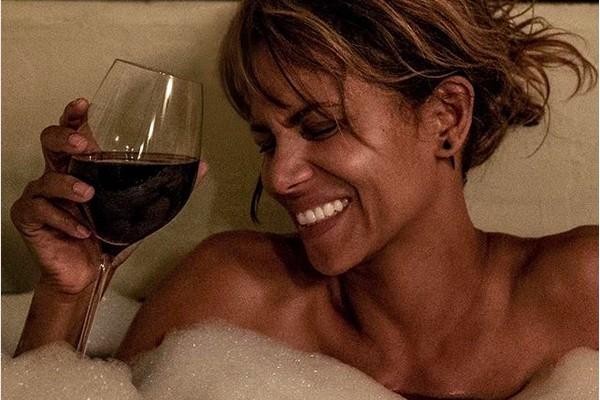 A atriz Halle Berry sorrindo e tomando banho de banheira enquanto bebe vinho (Foto: Instagram)