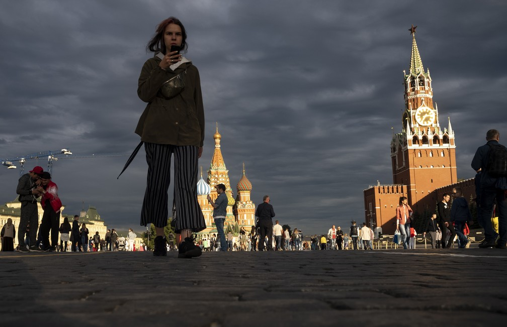 Mulher caminha ao pôr do sol na Praça Vermelha, em Moscou. — Foto: Alexander Zemlianichenko/AP