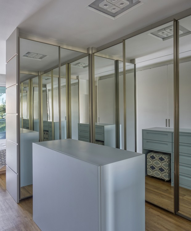 Portas espelhadas fecham os armários do closet, que ganhou uma ilha central  (Foto: MCA Estúdio/Divulgação/Produção: Núria Uliana)