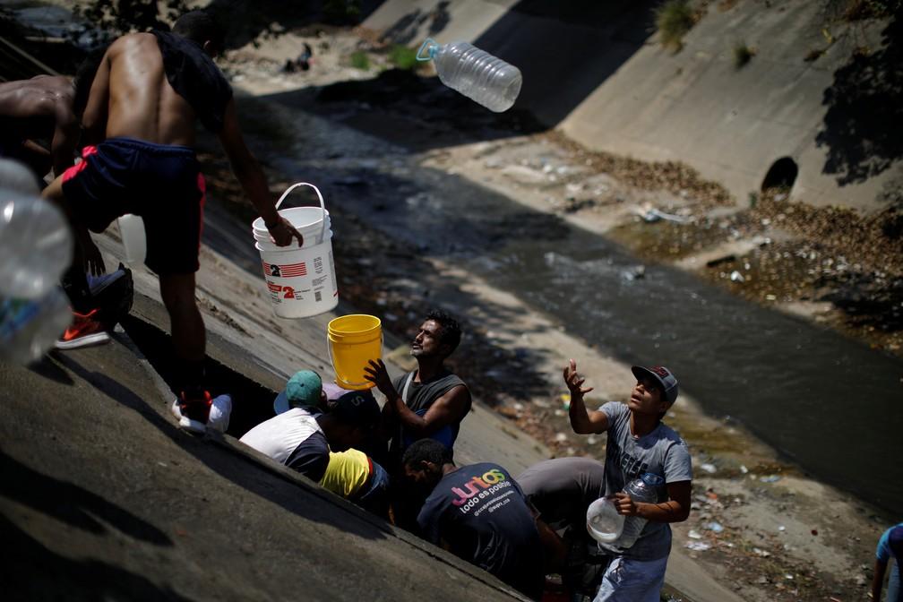 Venezuelanos coletam água de esgoto que corre para o Rio Guaire — Foto: Reuters/Carlos Garcia Rawlins