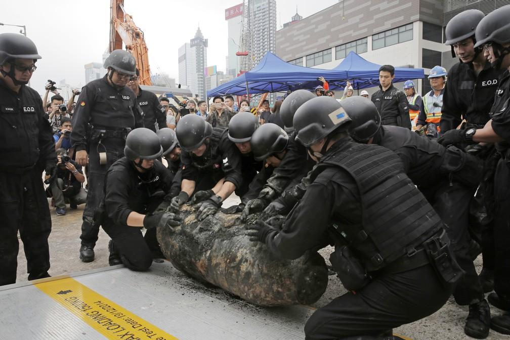 Policiais movem nesta sexta-feira (11) uma bomba desativada descoberta durante obras do metrô em Hong Komg (Foto: Kin Cheung/ AP Photo)