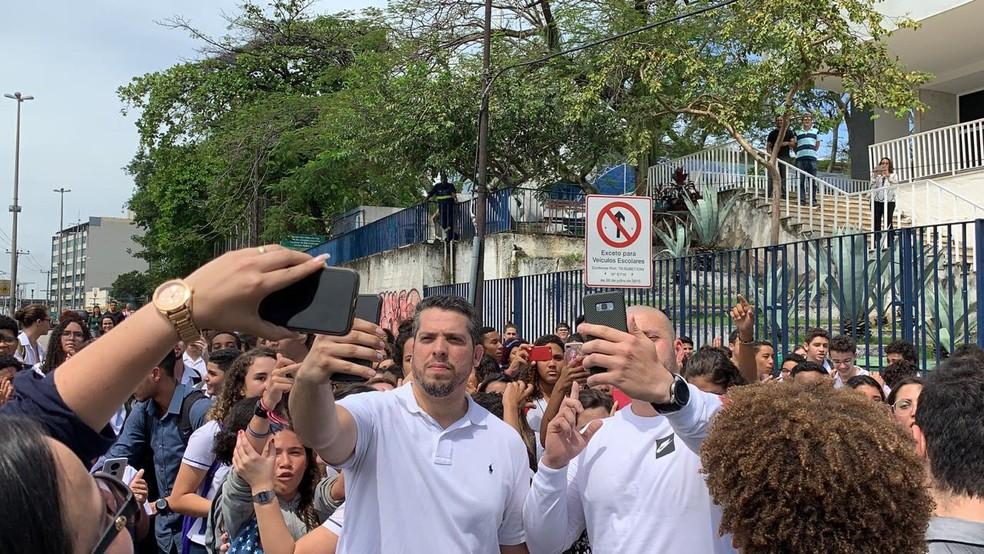 Deputados Rodrigo Amorim (E) e Daniel Silveira tiram selfies após visita ao Colégio Pedro II de São Cristóvão — Foto: Matheus Rodrigues/G1