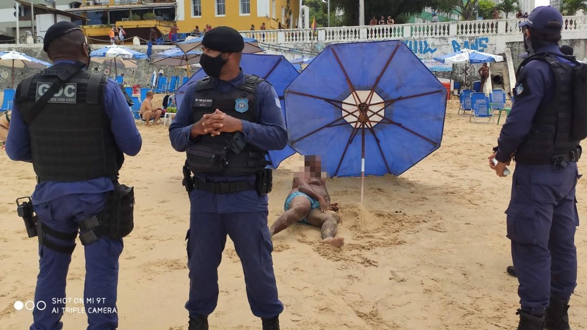 Homem com transtornos mentais é contido por guardas municipais na praia do Porto da Barra, em Salvador; faca foi apreendida
