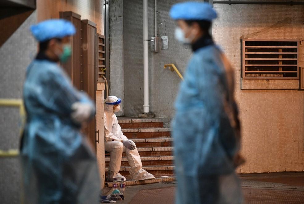 Equipe médica acompanha evacuação de prédio em Hong Kong onde foram encontrados dois casos suspeitos de coronavírus — Foto: Anthony Wallace/AFP