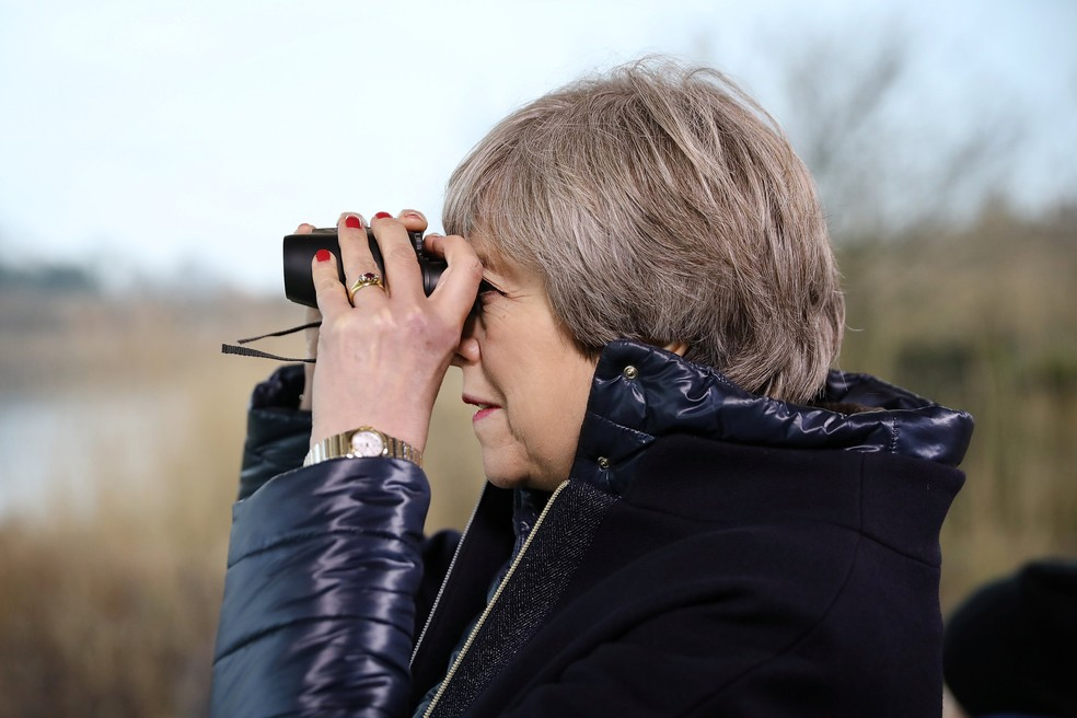 Primeira-ministra do Reino Unido, Theresa May, observa pássaros em Londres (Foto: Dan Kitwood/Reuters)