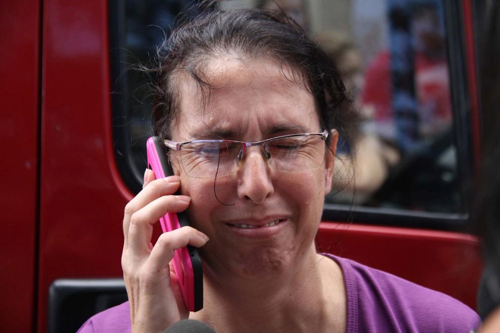 Uma mulher fala no celular enquanto aguarda por novidades na entrada da Escola Estadual Raul Brasil em Suzano, na Grande São Paulo. Dois criminosos encapuzados mataram oito pessoas no local e cometeram suicídio em seguida — Foto: Maurício Sumiya/Futura Press via AP