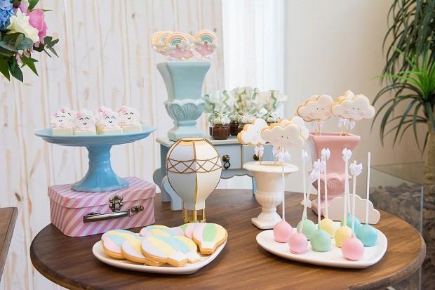 Na mesa auxiliar, biscoitos em formato de balões e nuvens dividem espaço com pirulitos de arco-íris, cake-pops coloridos e bombons. Para ganhar altura, Suellen posicionou uma malinha e um gaveteiro  (Foto: Danilo Giunchetti)