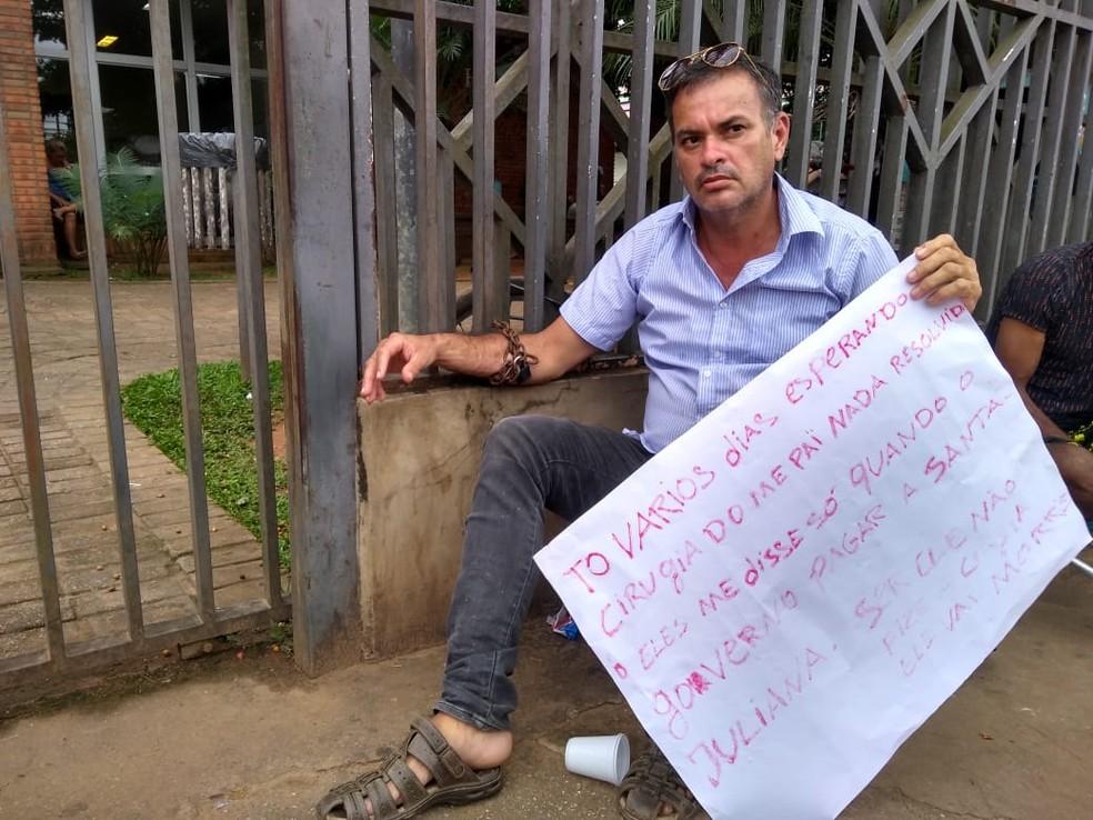 Francisco Cavalcante se acorrentou em frente ao Huerb para pedir que cateterismo do pai seja feito — Foto: Alcinete Gadelha/G1