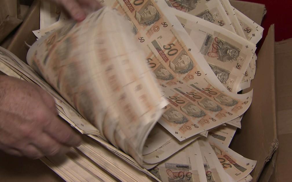 Folhas com dinheiro falso que foi impresso na Zona Norte de SP (Foto: Reprodução/TV Globo)