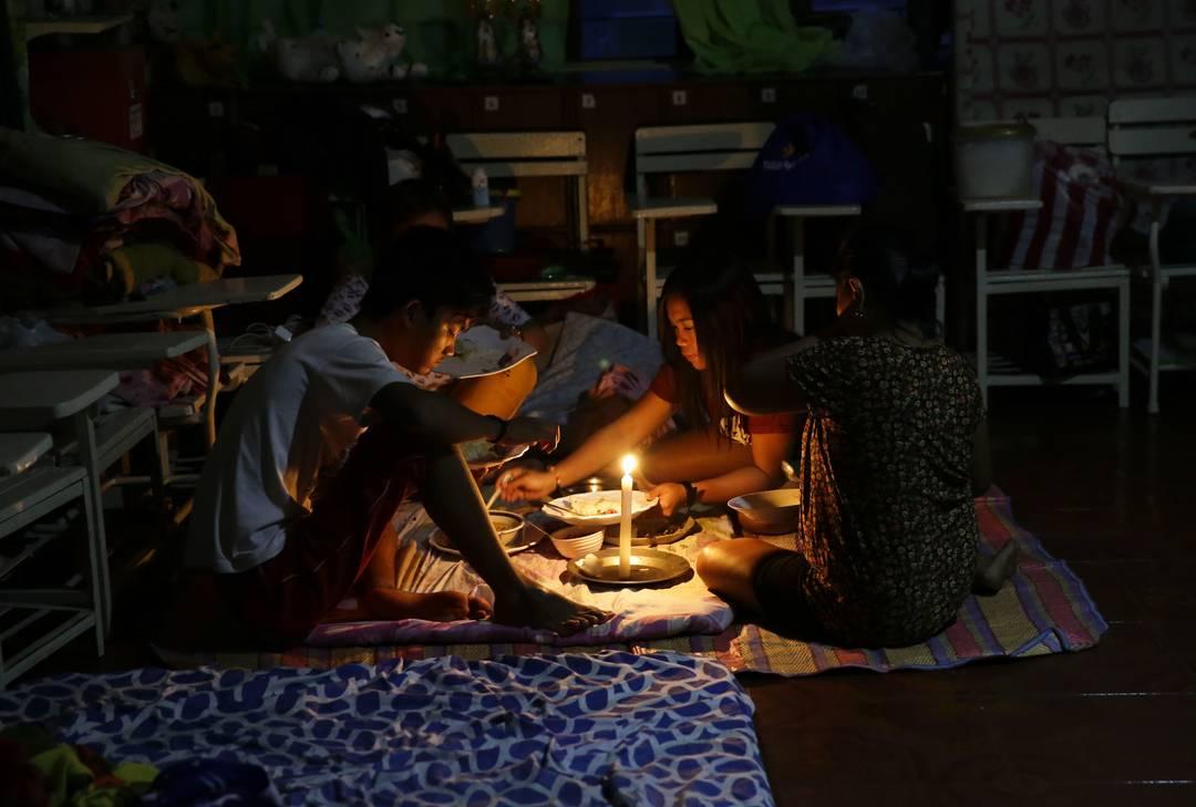 Família compartilha uma refeição usando velas dentro de um centro de evacuação temporária na cidade de Tuguegarao, província de Cagayan, no nordeste das Filipinas