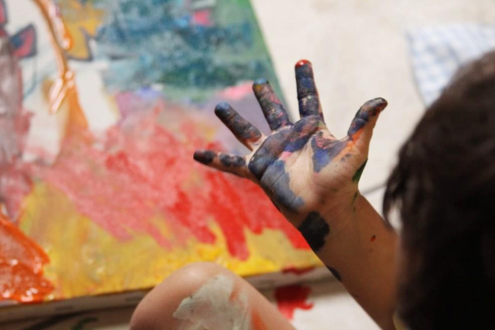 Mateus foi perdendo a rejeição que tinha à sujeira, conseguiu pintar não só com os pincéis, mas também com as próprias mãos — Foto: Milton Rosa/Arquivo Pessoal