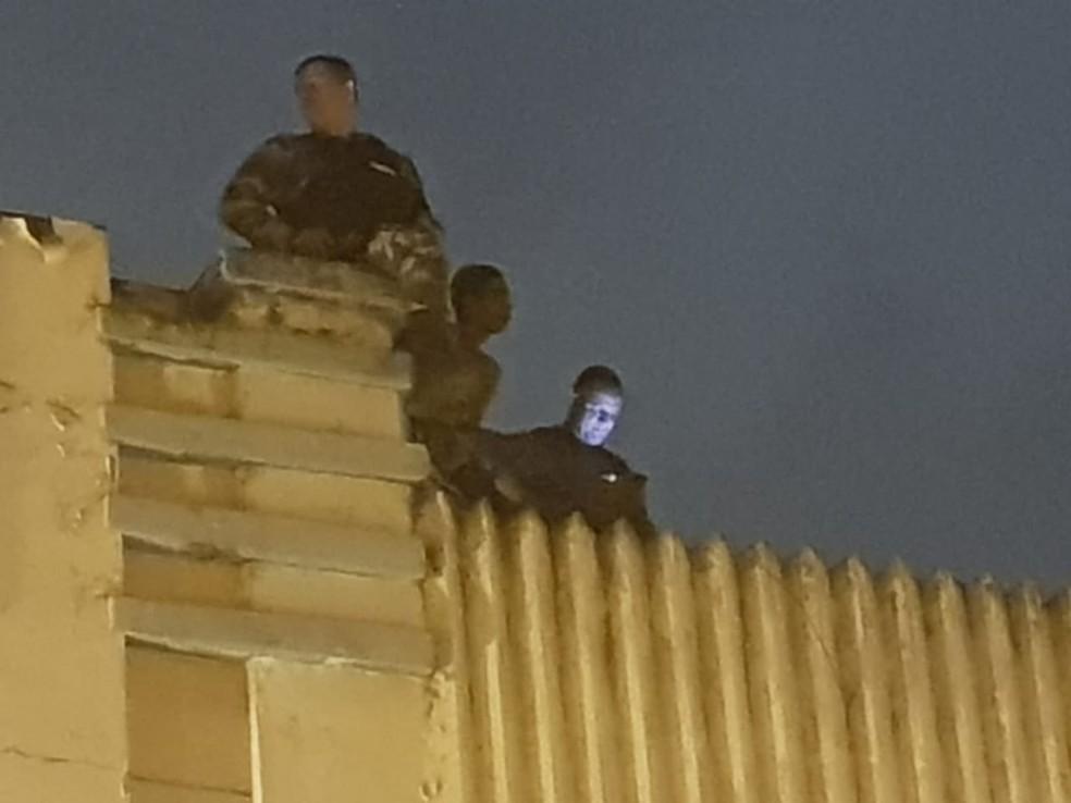 Suspeito foi encontrado dentro de caixa d'água, em cima do telhado das lojas, em Campina Grande — Foto: Soldado R Araújo/PMPB