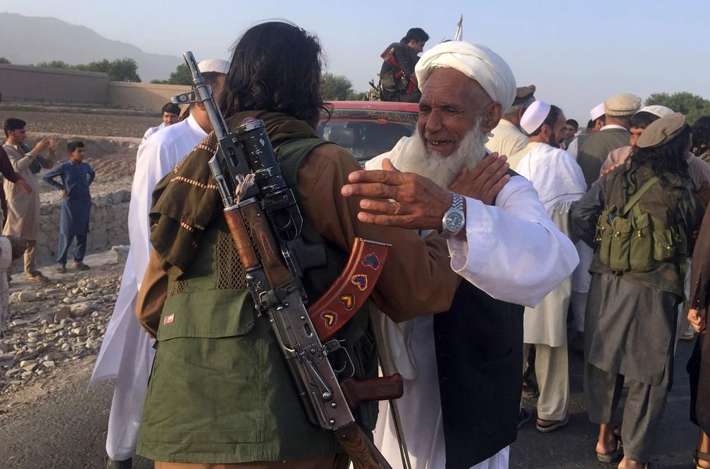 Foto de junho de 2018 mostra combatentes talibãs comemorando com moradores uma trégua de 3 dias organizada por causa do feriado muçulmano do Eid al-Fitr, na província de Nangarhar  — Foto: Rahmat Gul/AP