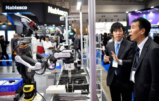 Dois participantes observam um robô industrial em uma feira de robótica em Tóquio (Foto: Franck Robichon / EFE / El País)