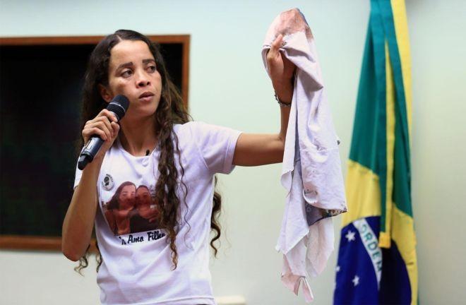 Bruna Silva levou a camisa do uniforme escolar do filho, manchada de sangue, para protestos, entrevistas, encontros com autoridades. Aqui, ela aparece em depoimento à Câmara dos Deputados, em julho de 2018 (Foto: CÂMARA DOS DEPUTADOS via BBC News Brasil)