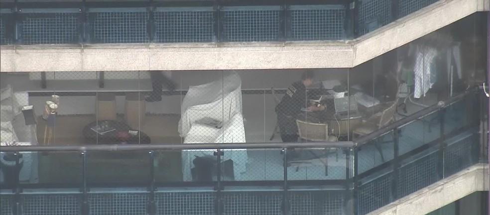 Agente da Polícia Federal na varanda do prédio do ex-chefe da Casa Civil do governo Cabral, Régis Fichtner. (Foto: Reprodução/ TV Globo)