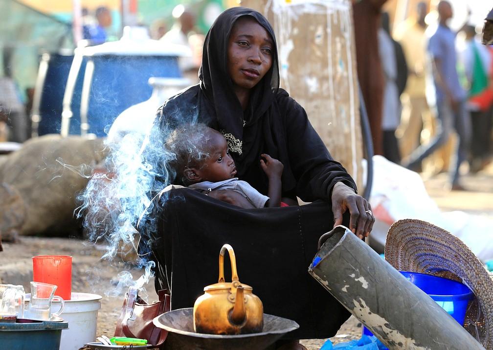 30 de abril - Uma vendedora de rua oferece chá a passantes enquanto segura seu bebê, em Cartum, Sudão — Foto: Umit Bektas/Reuters