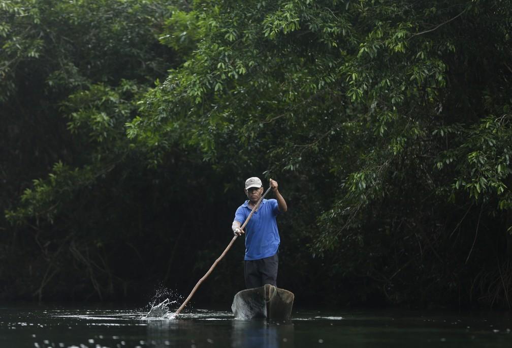 Homem navega em pequeno barco perto da comunidade de El Terrón, no Panamá, onde integrantes de seita mataram sete pessoas — Foto: Arnulfo Franco/AP