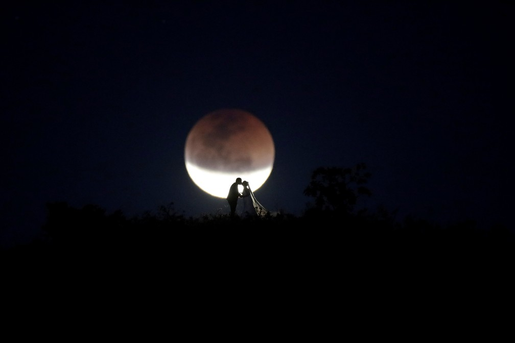 Noivos se beijam com a lua em eclipse ao fundo, em Brasília. (Foto: Ueslei Marcelino/Reuters)
