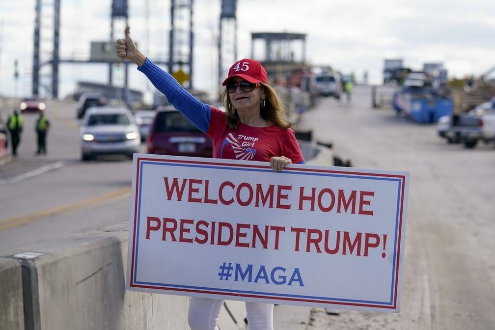 Uma apoiadora do presidente Donald Trump espera a carreata na estrada para Mar-a-Lago, propriedade de Trump em Palm Beach, na Flórida, nesta quarta-feira (20)  — Foto: Lynne Sladky/AP