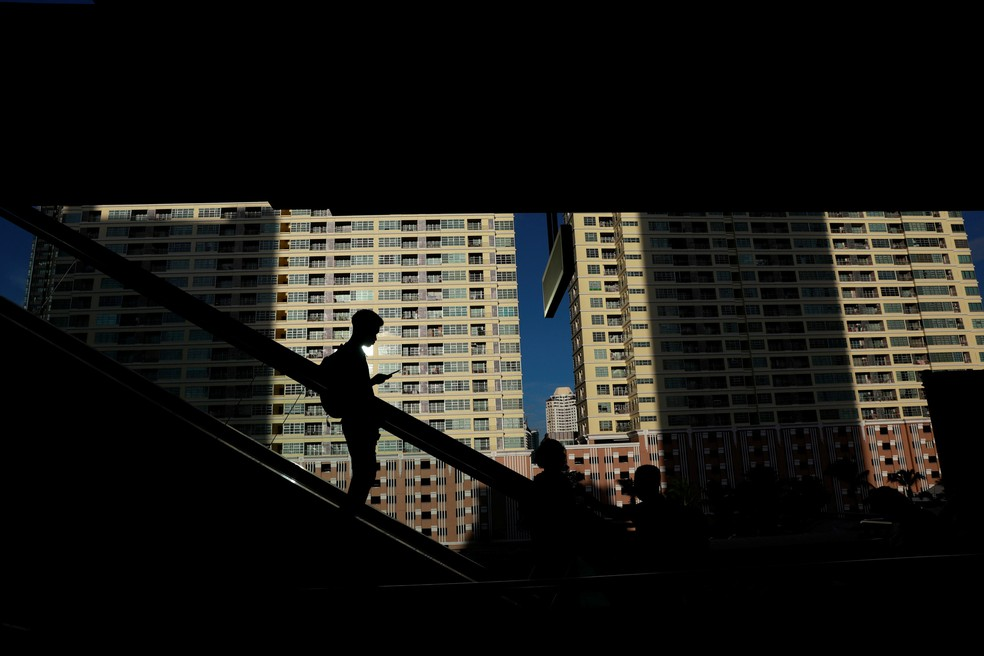 Um homem utiliza seu telefone celular enquanto desce na escada rolante de uma estação de trem em Bangkok, na Tailândia — Foto: Soe Zeya Tun/Reuters