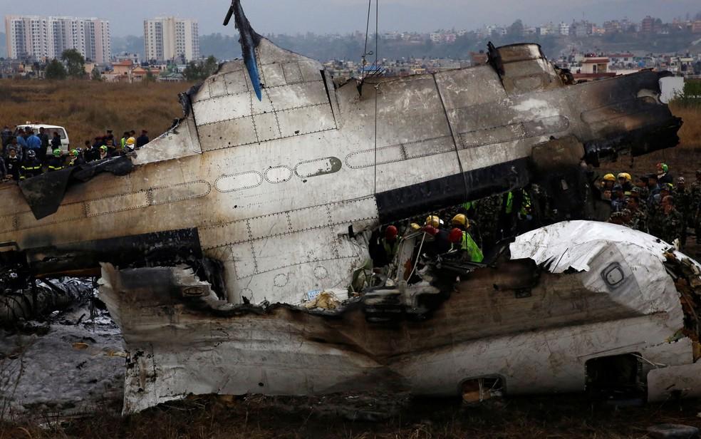 Funcionários trabalham nos destroços do avião US-Bangla que caiu no Tribhuvan International Airport, em Katmandu, no Nepal, na segunda-feira (12)  (Foto: Reuters/ Navesh Chitrakar)