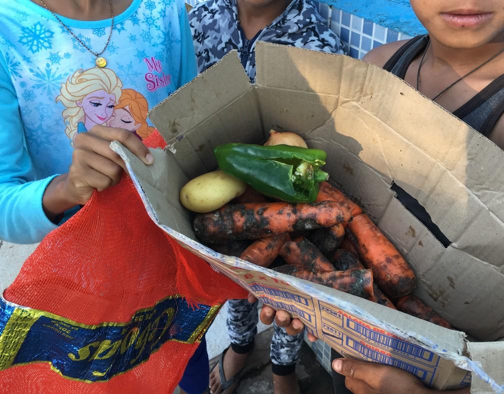 Irmãos venezuelanos, de 9 e 11 anos, e amigo, de 12, seguram caixa com alimentos que conseguiram pegar no meio do lixo em Pacaraima, na fronteira com a Venezuela — Foto: Emily Costa/G1 RR