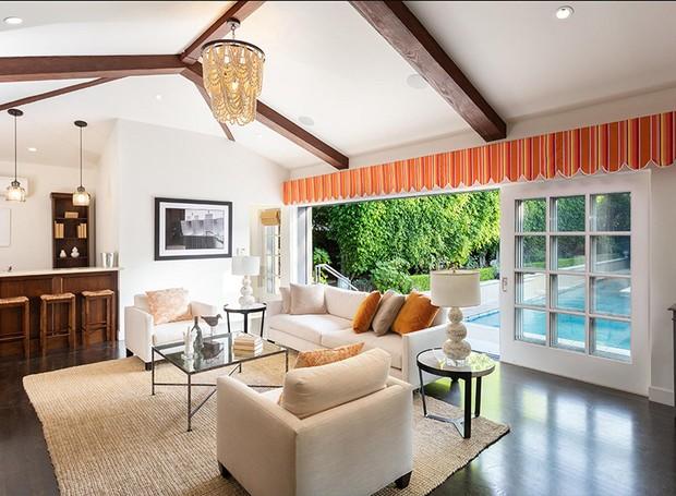 A sala de entretenimento oferece bar e tem vista para a piscina (Foto: Berkshire Hathaway HomeServices/ Reprodução)