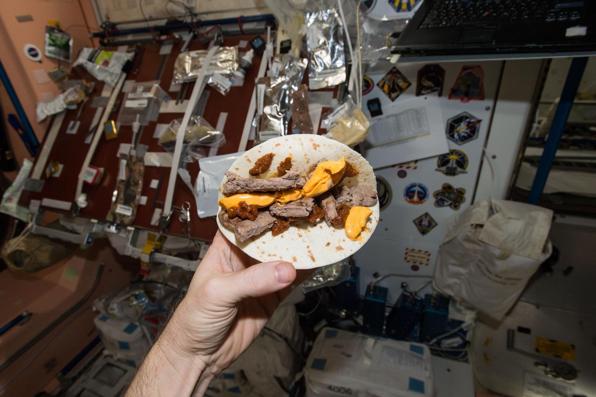 """O engenheiro espacial da NASA, Terry Virts, mostra o seu """"hambúrguer espacial"""" feito com tortilla para substituir o pão  (Foto: NASA)"""