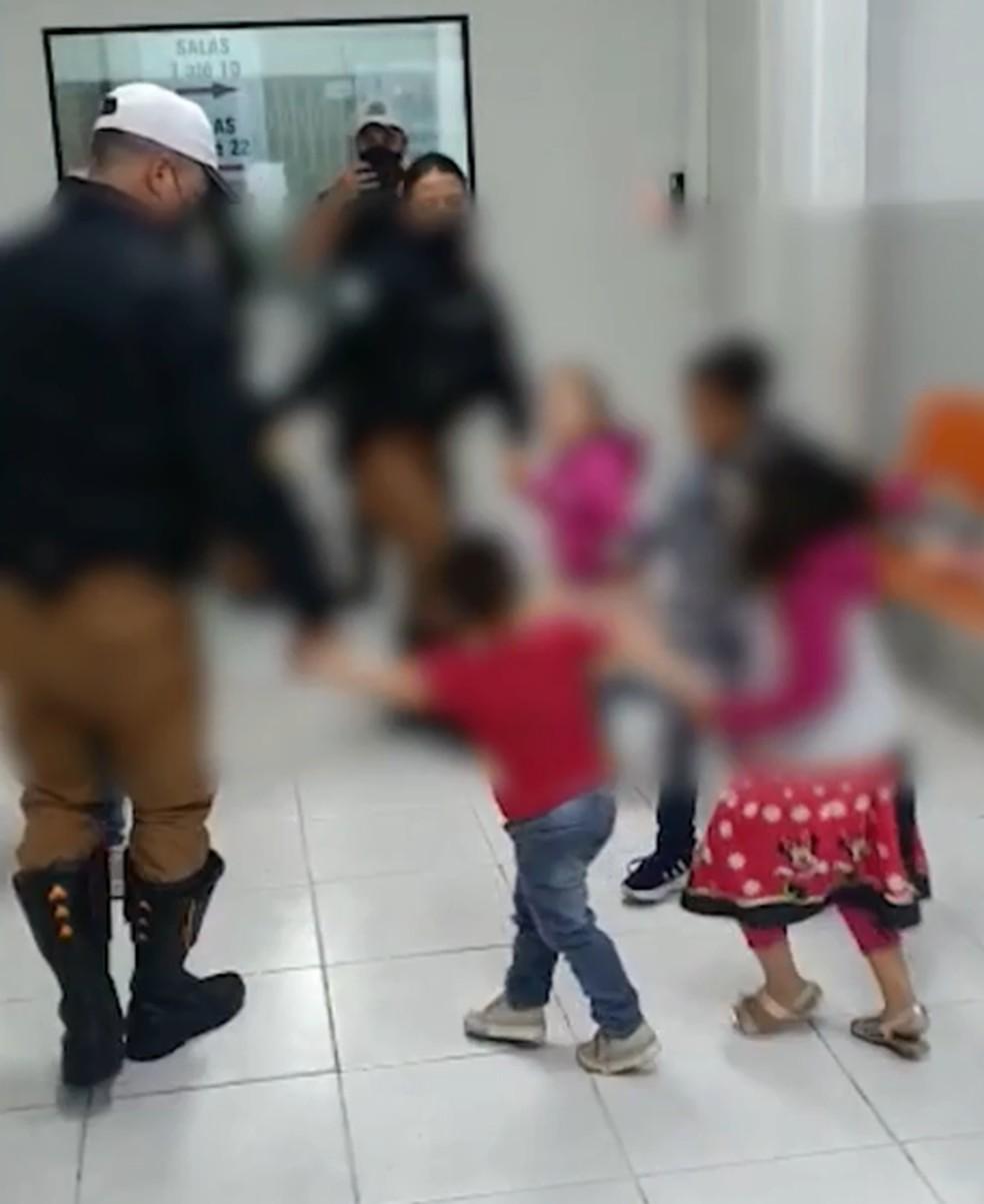 Policiais brincam de roda com crianças, após pais serem presos suspeitos de tráfico de drogas — Foto: Divulgação/BPTran