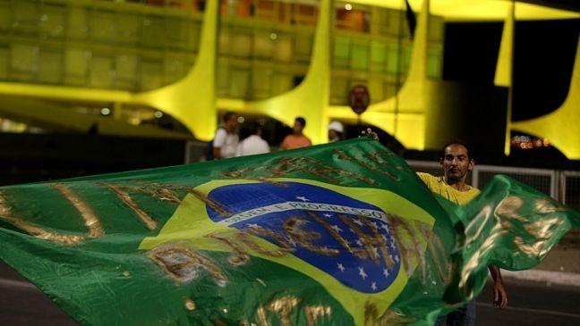 Manifestantes estendem bandeira do Brasil em frente ao Palácio do Planalto nesta sexta (Foto: Nilton Fukuda / Estadão)