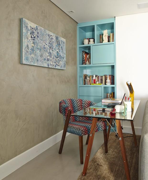 Mesa de escritório com tampo de vidro da Clami, poltrona da Clami com tecido estampado da Farm, e estante laqueada de azul ao fundo. Apartamento da jornalista Priscila Dal Poggetto, cujo projeto de decoração é da designer de interiores Helena Kallas (Foto: Victor Affaro / Editora Globo)