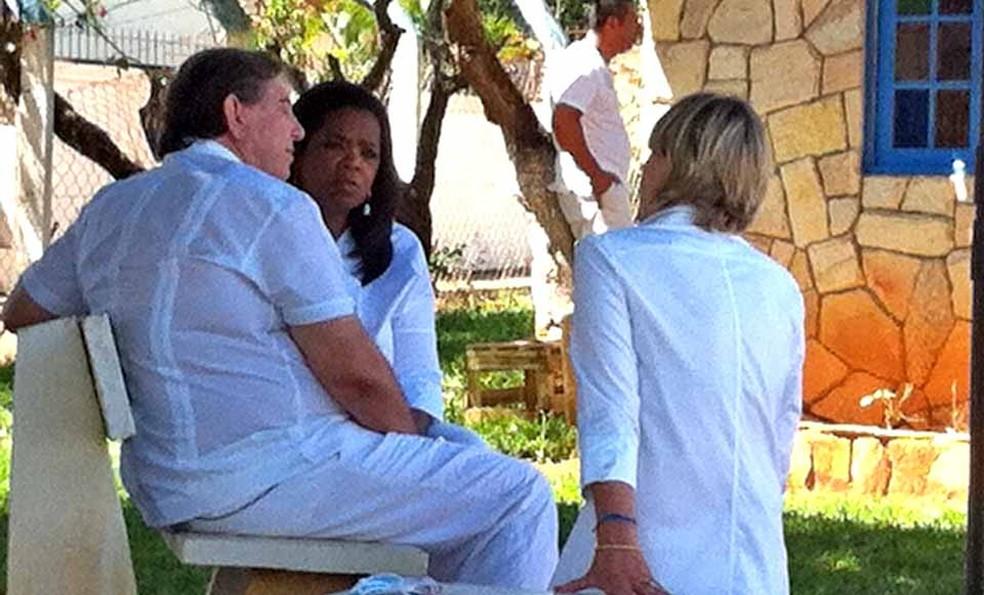 A apresentadora Oprah Winfrey conversa com o médium João de Deus sob uma árvore na Casa Dom Inácio de Loyola — Foto: Rafaela Céo/G1